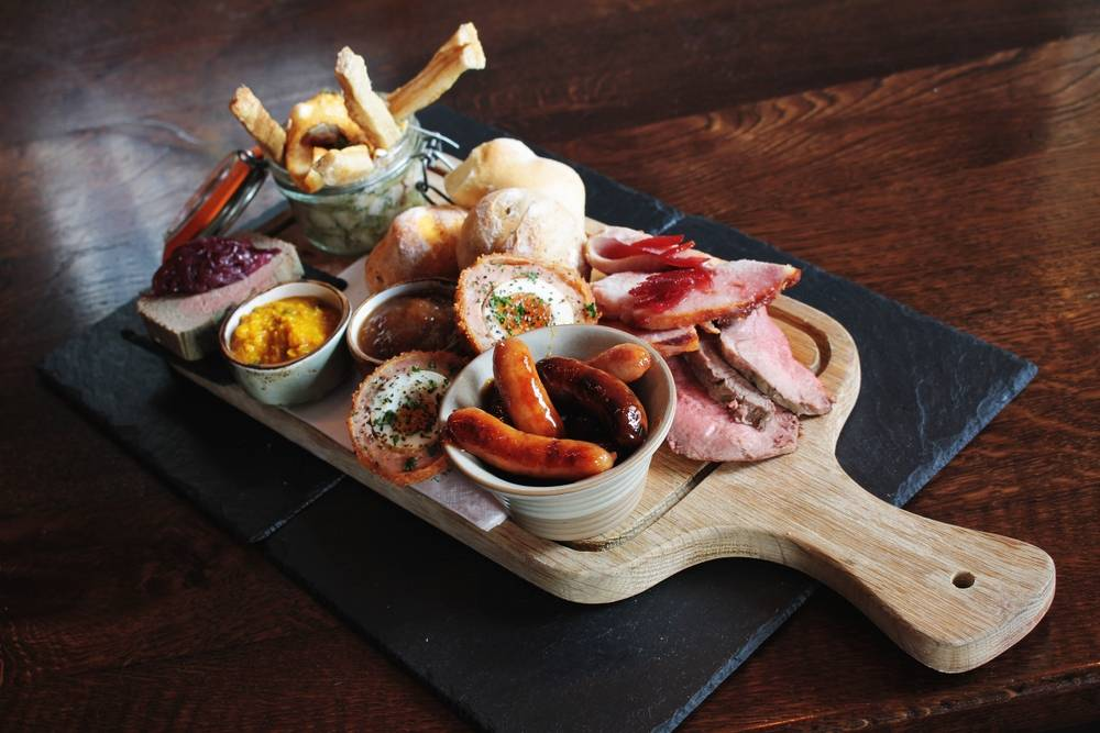 Sharing Platter At The Boars Head served on a paddle board with a variety of bar snacks